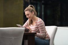 Szczęśliwy kobieta uczeń W kawiarni Z dotyka ochraniaczem Obrazy Royalty Free