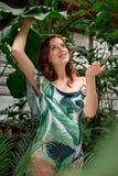 Szczęśliwy kobieta w ciąży w kwiecistym swimsuit przy greenery fotografia royalty free