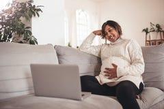 Szczęśliwy kobieta w ciąży na kanapie używać laptop Zdjęcie Stock