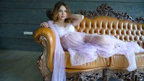 Szczęśliwy kobieta w ciąży odpoczywa na kanapie i muska jej brzuszek zdjęcie wideo