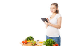 Szczęśliwy kobieta w ciąży z ochraniaczem i warzywami na stole Zdjęcia Royalty Free