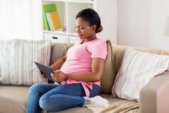 Szczęśliwy kobieta w ciąży z pastylka komputerem osobistym w domu Obrazy Royalty Free