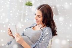 Szczęśliwy kobieta w ciąży z pastylka komputerem osobistym w domu Zdjęcie Stock