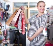 Szczęśliwy kobieta w ciąży z torba na zakupy w odzież sklepie na sklepie fotografia royalty free