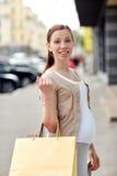 Szczęśliwy kobieta w ciąży z torba na zakupy przy miastem Obraz Stock