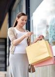 Szczęśliwy kobieta w ciąży z torba na zakupy przy miastem Fotografia Stock