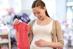Szczęśliwy kobieta w ciąży zakupy przy sklepem odzieżowym Fotografia Royalty Free