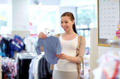 Szczęśliwy kobieta w ciąży zakupy przy sklepem odzieżowym Zdjęcia Royalty Free