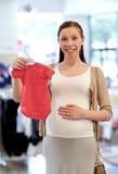 Szczęśliwy kobieta w ciąży zakupy przy sklepem odzieżowym Obraz Royalty Free