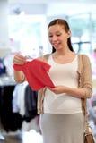 Szczęśliwy kobieta w ciąży zakupy przy sklepem odzieżowym Zdjęcie Stock