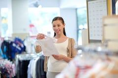 Szczęśliwy kobieta w ciąży zakupy przy sklepem odzieżowym Obrazy Stock