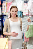 Szczęśliwy kobieta w ciąży zakupy przy sklepem odzieżowym Obrazy Royalty Free