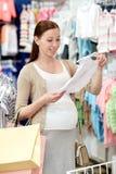 Szczęśliwy kobieta w ciąży zakupy przy sklepem odzieżowym Fotografia Stock