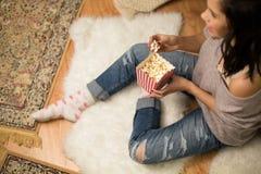 Szczęśliwy kobiety łasowania popkorn w domu obrazy royalty free