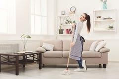 Szczęśliwy kobiety cleaning dom z kwacza i mieć zabawą zdjęcia royalty free