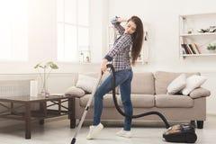 Szczęśliwy kobiety cleaning dom z próżniowym cleaner zdjęcia royalty free
