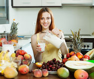 Szczęśliwy kobiety dolewania mleka koktajl z owoc Fotografia Stock