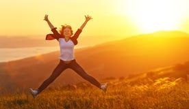 Szczęśliwy kobiety doskakiwanie i cieszyć się przy zmierzchem w górach życie Zdjęcia Stock