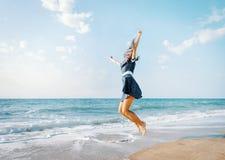 Szczęśliwy kobiety doskakiwanie na plaży na wakacjach zdjęcie stock