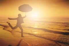 Szczęśliwy kobiety doskakiwanie w morze plaży zmierzchu sylwetce Obrazy Stock