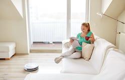 Szczęśliwy kobiety i robota próżniowy cleaner w domu obrazy royalty free