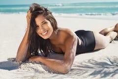 Szczęśliwy kobiety lying on the beach na piasku Obrazy Royalty Free
