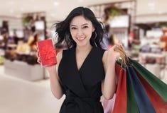 Szczęśliwy kobiety mienia prezenta pudełko i torba na zakupy przy centrum handlowym obrazy royalty free