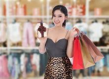 Szczęśliwy kobiety mienia prezenta pudełko i torba na zakupy przy centrum handlowym obrazy stock