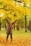 Szczęśliwy kobiety miotanie spadać liść zdjęcie stock