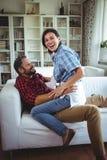 Szczęśliwy kobiety obsiadanie dalej obsługuje podołek w żywym pokoju zdjęcie stock