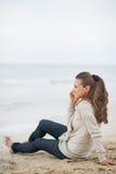 Szczęśliwy kobiety obsiadanie na osamotnionej plaży i opowiadać telefonie komórkowym zdjęcie royalty free