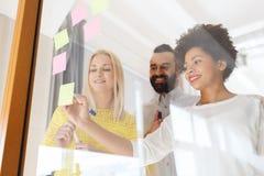 Szczęśliwy kreatywnie drużynowy writing na majcherach przy biurem Zdjęcie Royalty Free