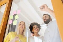 Szczęśliwy kreatywnie drużynowy writing na majcherach przy biurem Zdjęcia Royalty Free
