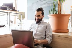 Szczęśliwy kreatywnie męski urzędnik z laptopem Zdjęcie Stock