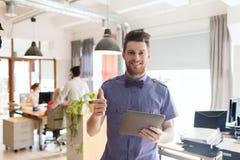 Szczęśliwy kreatywnie męski urzędnik z pastylka komputerem osobistym Zdjęcia Stock