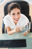 Szczęśliwy księgowy trzyma kalkulatora patrzeje kamerę Zdjęcia Stock