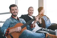 Szczęśliwy mężczyzna bawić się gitarę blisko kompanów zdjęcie stock
