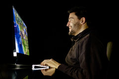 Szczęśliwy mężczyzna bawić się gra wideo na komputerze stacjonarnym Fotografia Stock