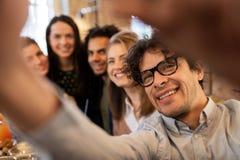 Szczęśliwy mężczyzna bierze selfie z przyjaciółmi przy restauracją fotografia royalty free