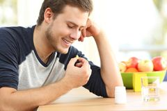 Szczęśliwy mężczyzna bierze witaminy pigułkę w domu fotografia royalty free