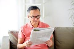 Szczęśliwy mężczyzna czyta gazetę w domu w szkłach Fotografia Stock