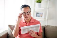 Szczęśliwy mężczyzna czyta gazetę w domu w szkłach Zdjęcie Royalty Free
