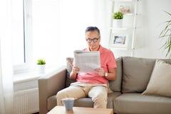 Szczęśliwy mężczyzna czyta gazetę w domu w szkłach Obraz Royalty Free