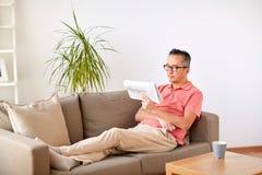 Szczęśliwy mężczyzna czyta gazetę w domu w szkłach Zdjęcia Stock