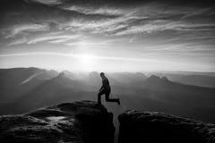 Szczęśliwy mężczyzna doskakiwanie między skałami, mgliste góry Zdjęcia Royalty Free