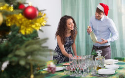 Szczęśliwy mężczyzna i dziewczyny porci bożych narodzeń stół dla gości obrazy stock