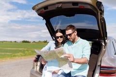 Szczęśliwy mężczyzna i kobieta z drogową mapą przy hatchback samochodem obrazy stock