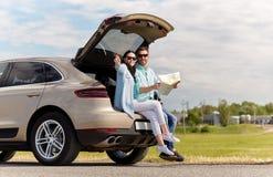 Szczęśliwy mężczyzna i kobieta z drogową mapą przy hatchback samochodem obraz stock