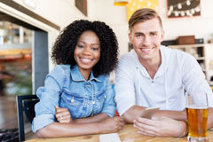 Szczęśliwy mężczyzna i kobieta z smartphone przy barem Fotografia Stock