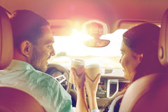Szczęśliwy mężczyzna i kobiety jeżdżenie w samochodzie z kawą zdjęcia stock